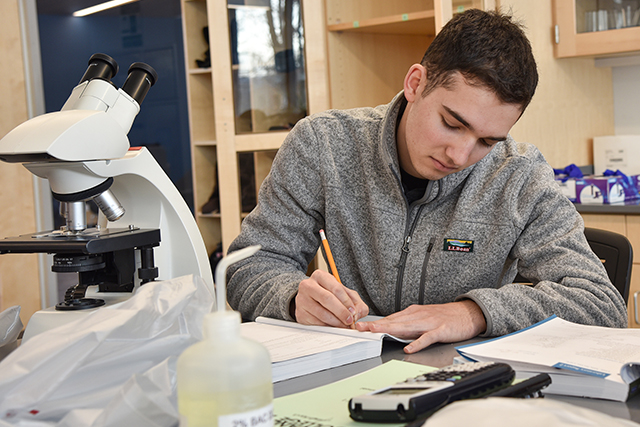 Student in science lab with microscope