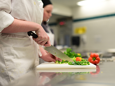 Culinary students chopping vegetables in the kitchen