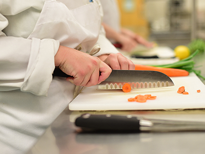 Culinary student chopping carrots