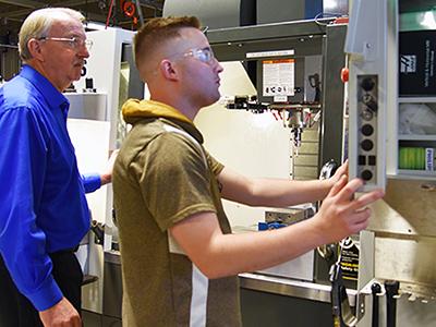 Machining instructor Dan Kepple guiding a student