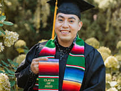 Emigdio Rincon wears his cap and gown, and a sash signaling he is a first-generation Latino college graduate
