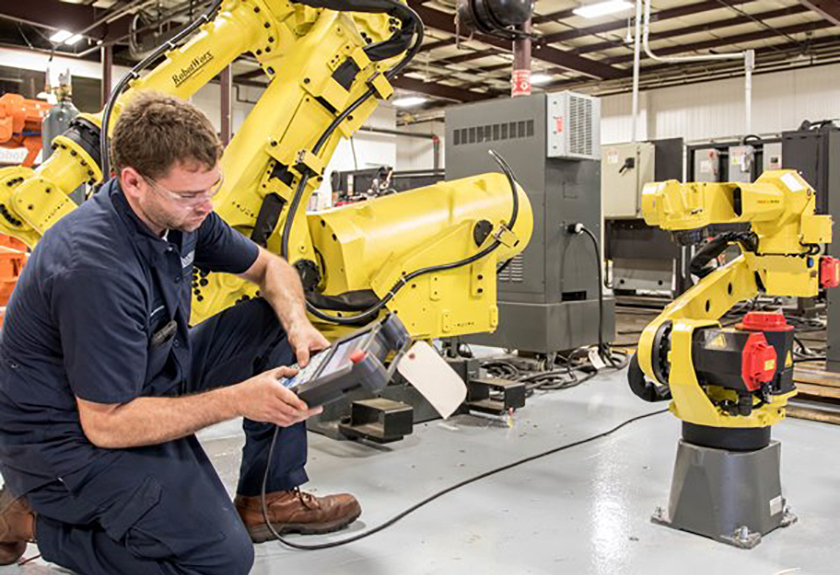 Worker checking robotics used in manufacturing